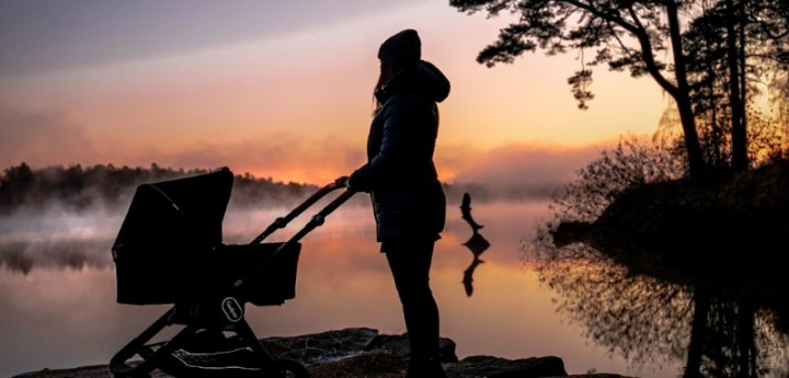 Mum with baby pram by a lake at sunrise