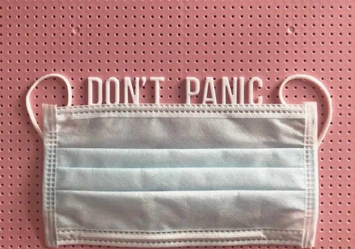 a white face mask on a pink background with the words Don't Panic above. worries