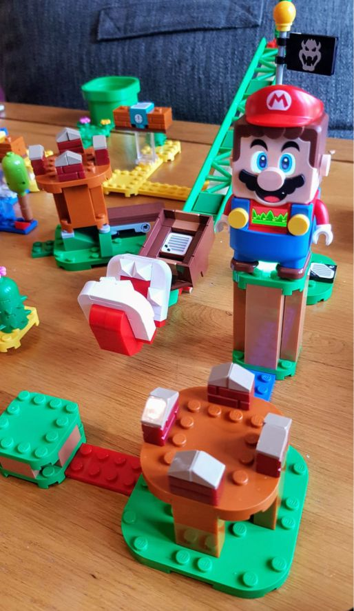 Lego Supermario, photo shows a lego set with a Super Mario figure standing on a tall block and lots of other lego pieces around him.