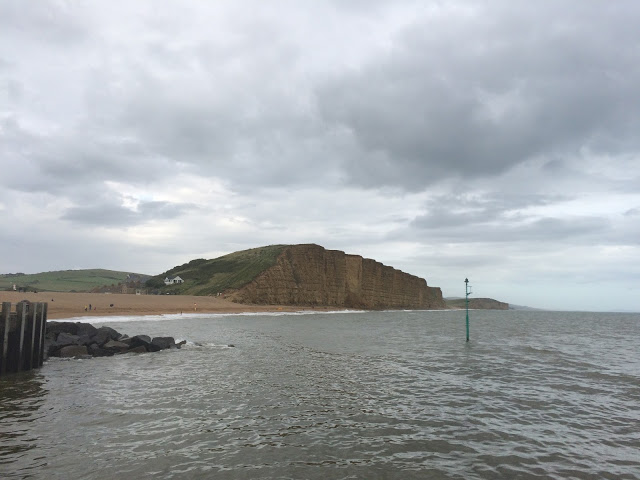 jurassic coastline in Dorset, taken in Charmouth. Image shows cloudy sky, cliffs and the sea