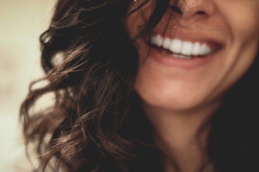 Image of woman with long dark curly hair and a big white smile.