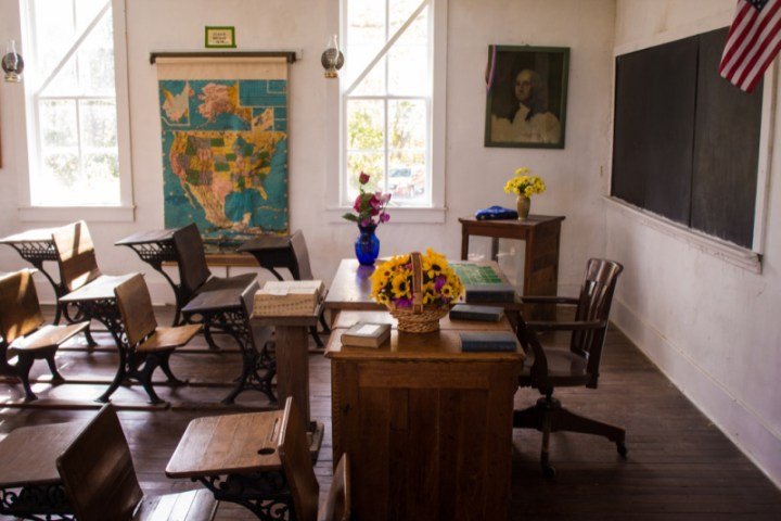stock photo of a classroom with wooden desks and vases of flowers.