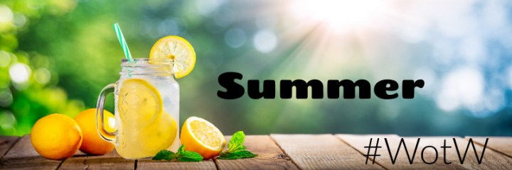 Summer, black text on image of a jug of lemonade with fresh lemons and the sun shining in the backgroun.