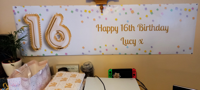 The special birthday banner with 16 and Happy Birthday on it along with matching presents unwrapped.