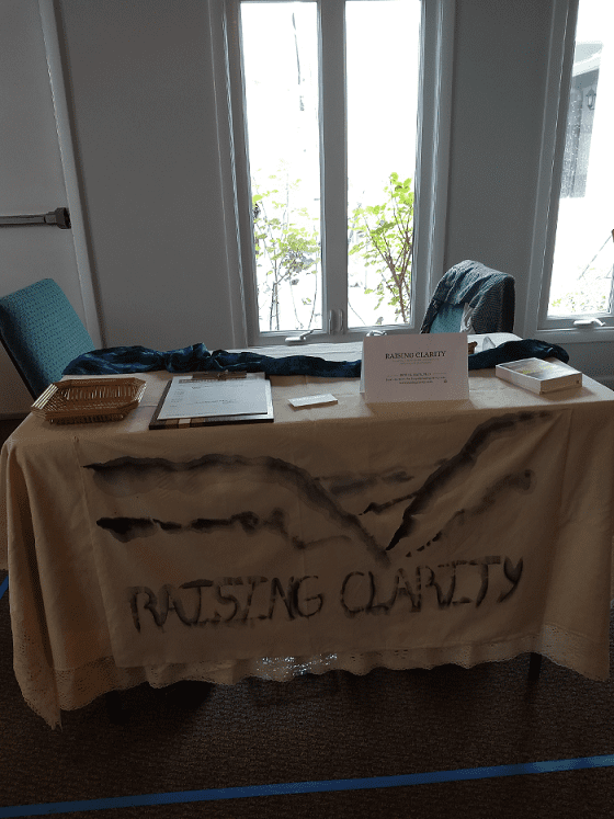 exhibitor table with a banner, chair behind it, and window behind the chair