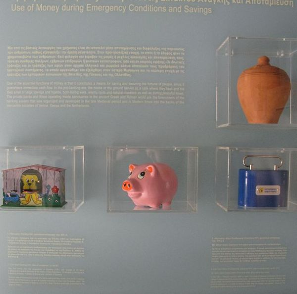 Museum display of various types of personal banks from piggy banks to ancient Greek clay container.