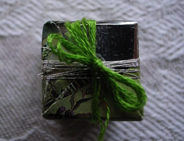 tiny silver-wrapped gift with a green yarn bow