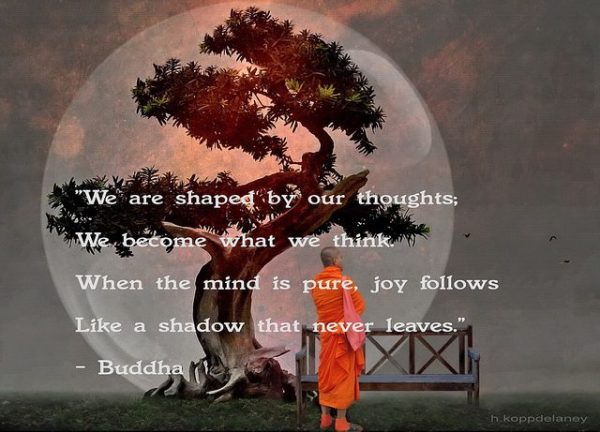 """sculptured curving tree and monk standing in front of a bench, with the quotation, """"We are shaped by our thoughts: we become what we think. When the mind is pure, joy follows like a shadow that never leaves,"""" attributed to the Buddha."""