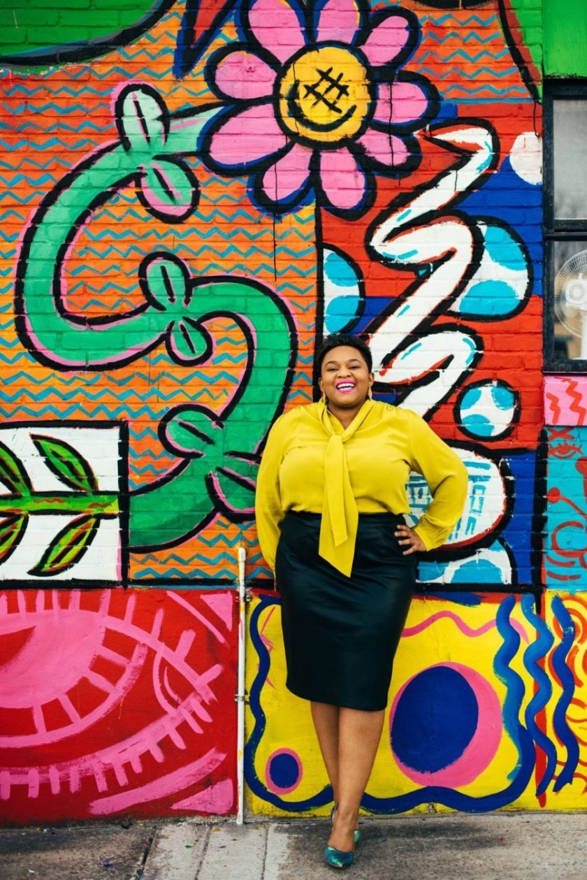 Smiling black woman in yellow top and black skirt against a very color painted brick wall
