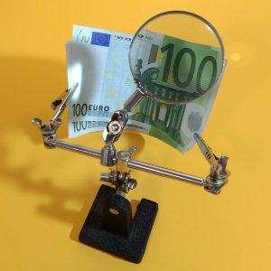 hombre lupa con billete de 100 euros