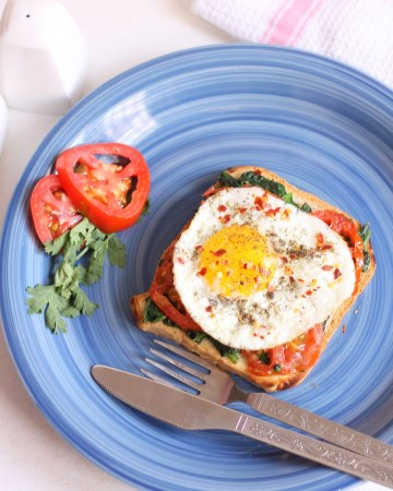 Open toast with fried egg tomato and spinach