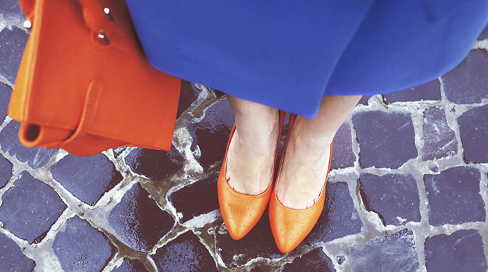 Women's legs in orange shoes. Bright orange shoes and bag. Blue coat, orange classic ladies shoes and tote bag. Rainy day. Street fashion. Street style. Business casual look. Autumn outfit.