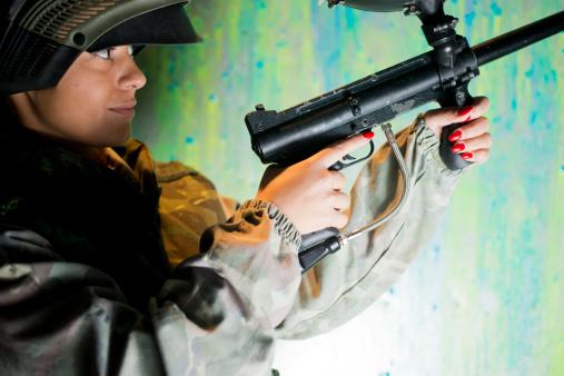 Woman playing paintball holding paintball gun