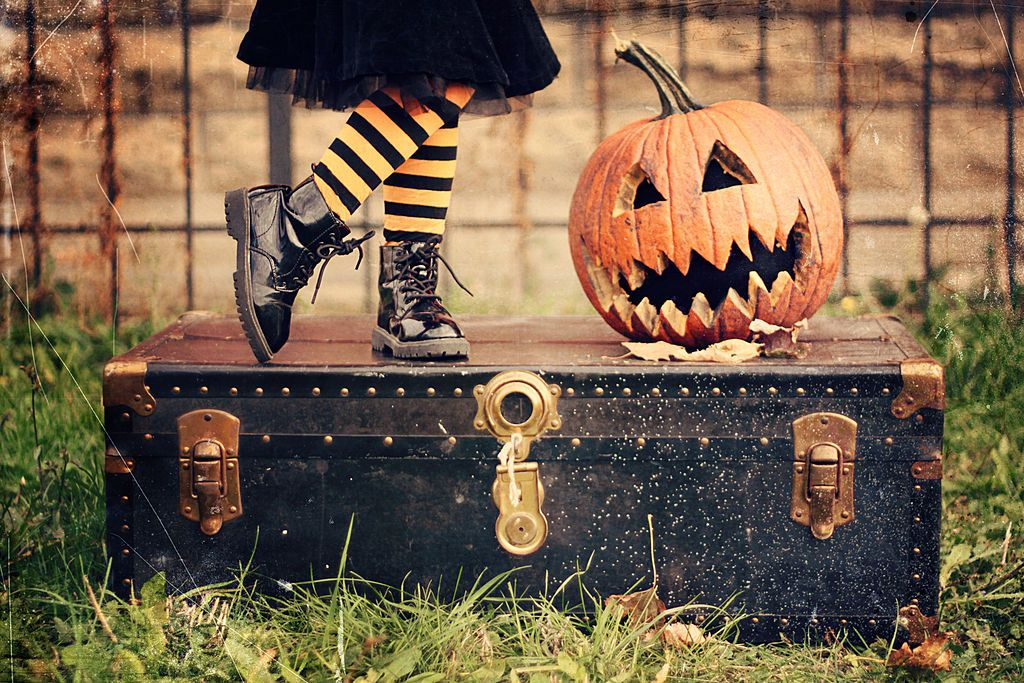 Little girl standing on a trunk next to a jack-o-lantern
