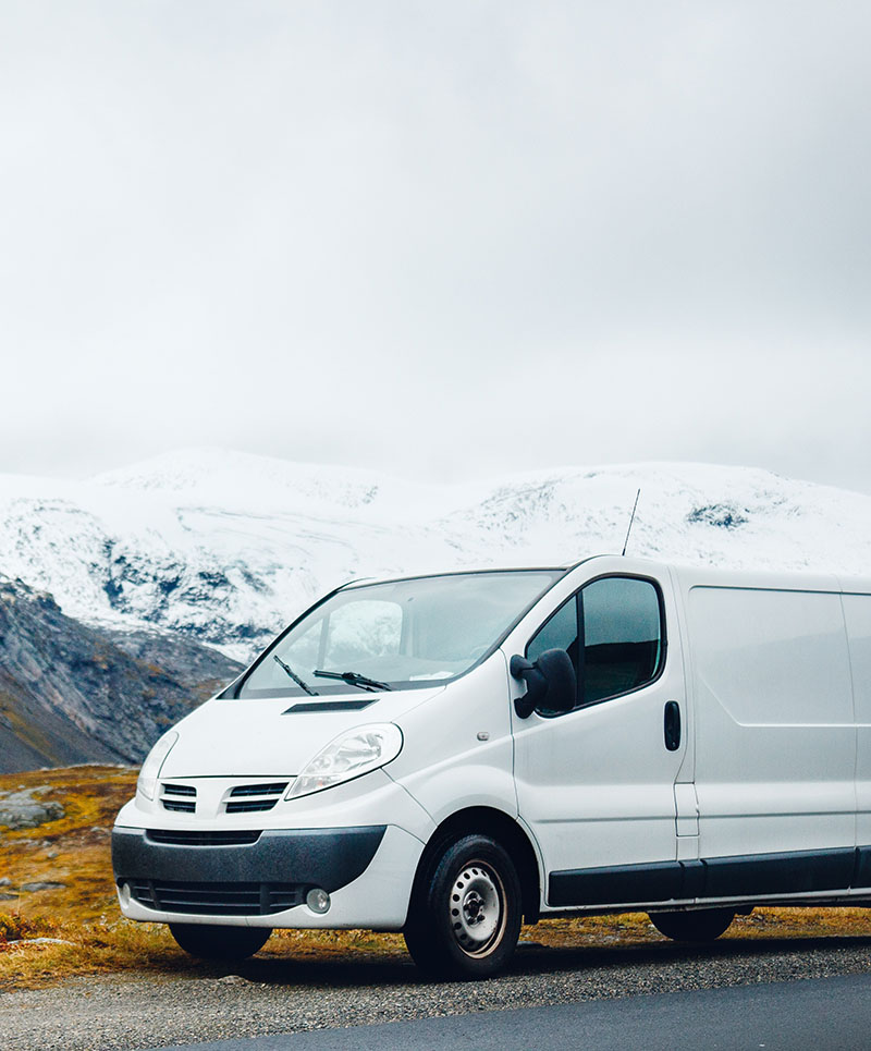 Van parked in front of a snowy mountain