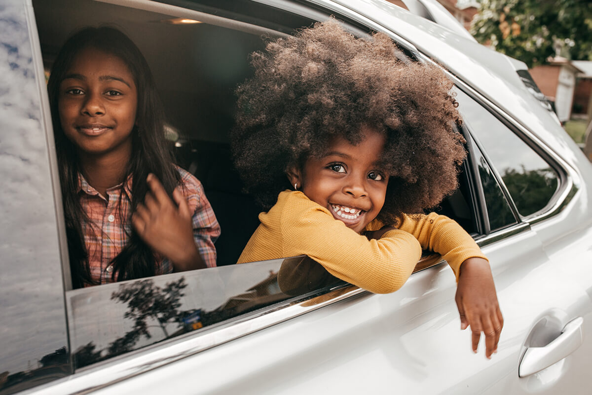 Child smiling out of a car window