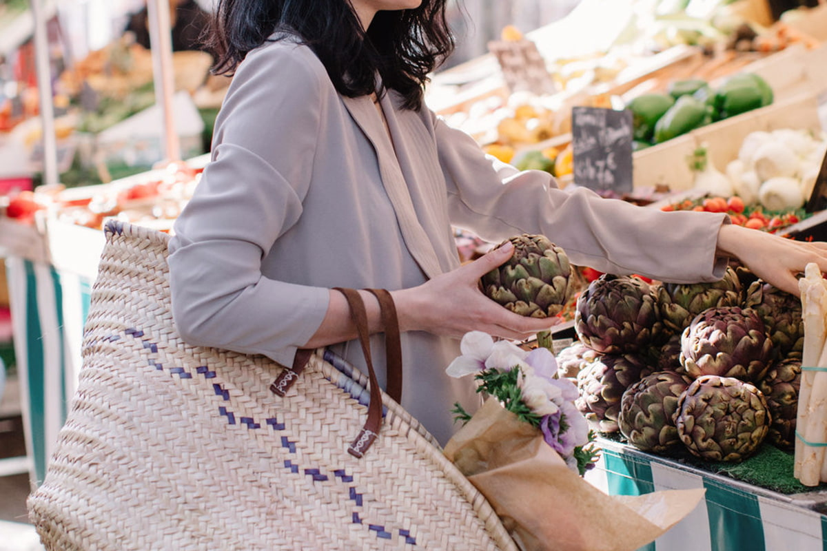 Woman carrying a shopping bag and buying produce