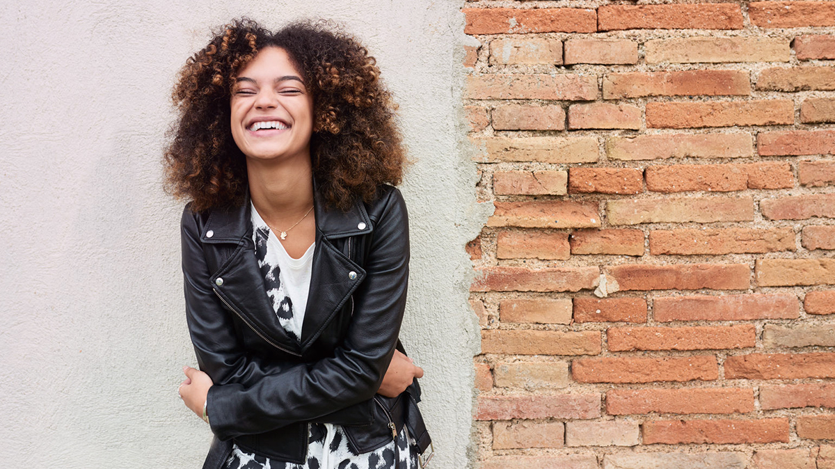 Women wearing a leather jacket laughing