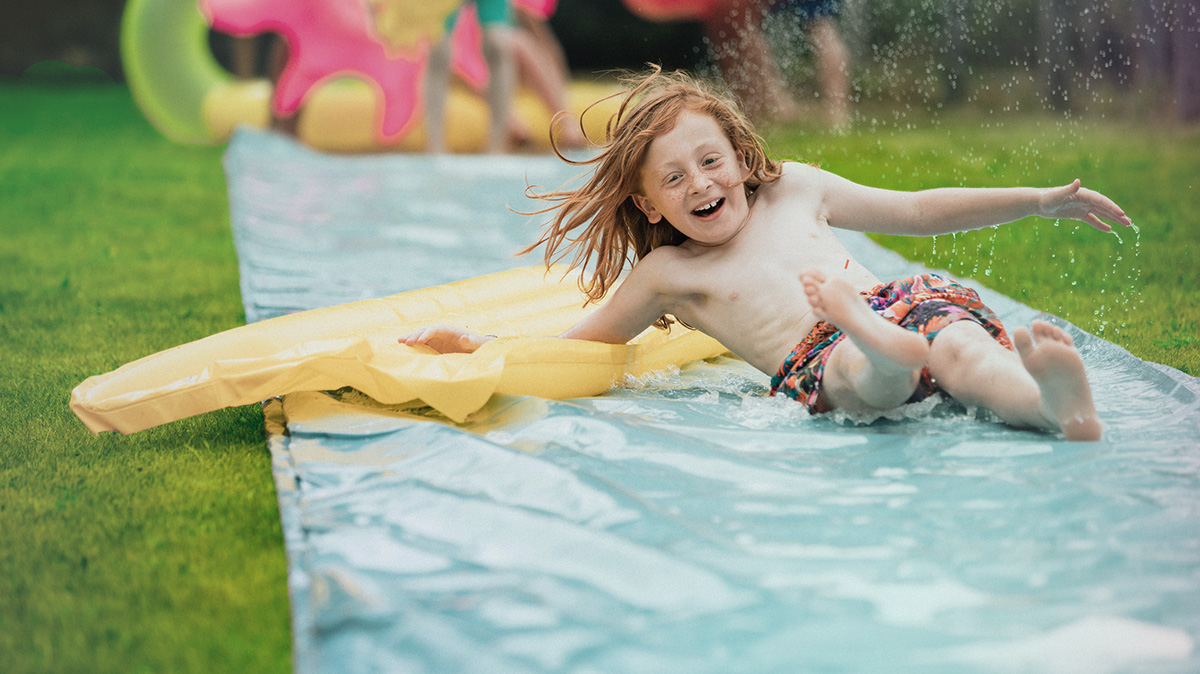 Young boy playing on slip 'n' slide