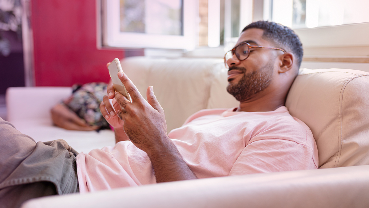 Guy using his phone on the couch