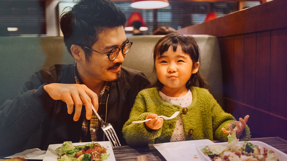 Dad and child eating at a restaurant