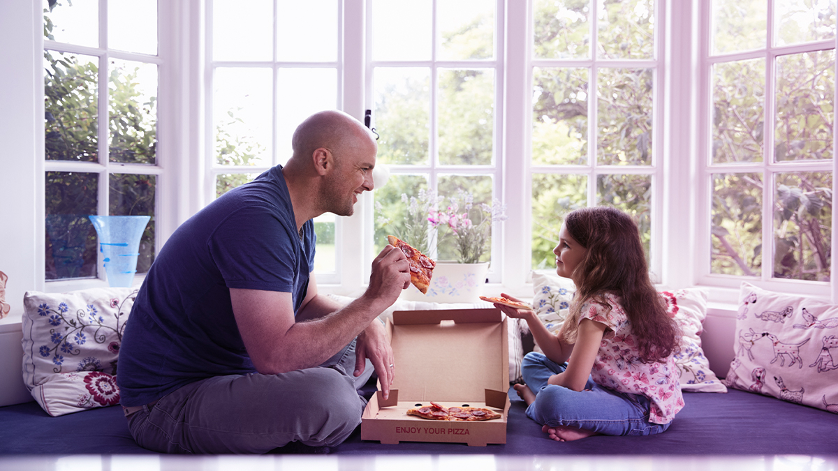 Dad and daughter eating pizza