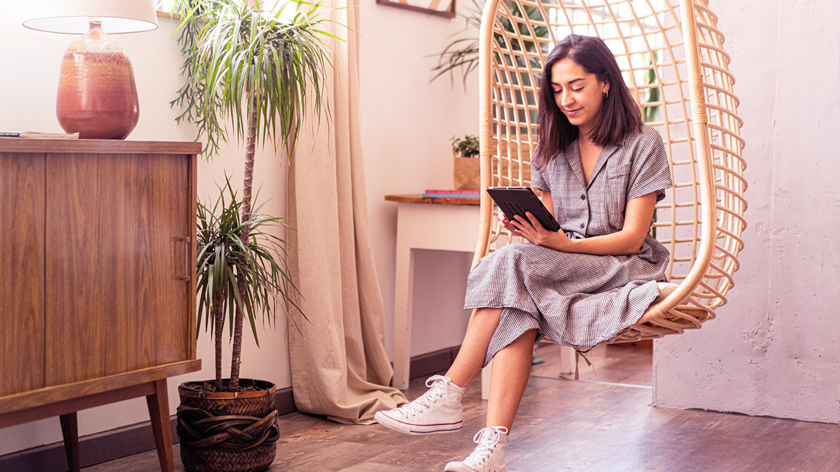 Girl in hanging chair on tablet