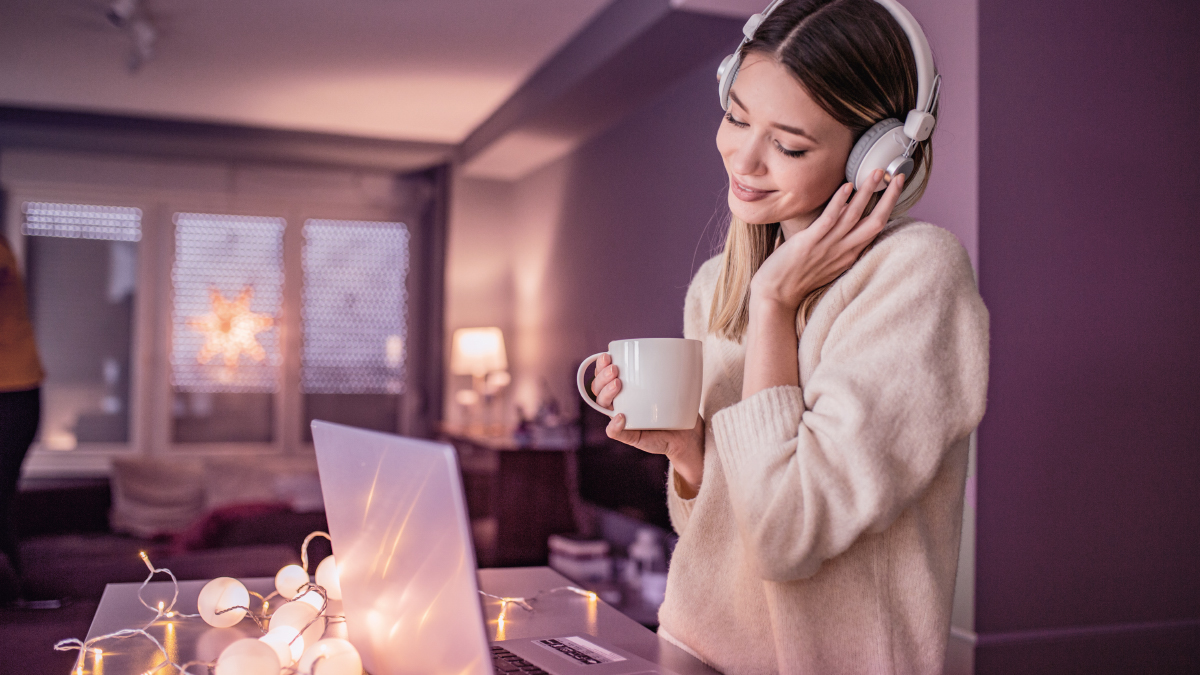 Woman wearing headphones and using laptop