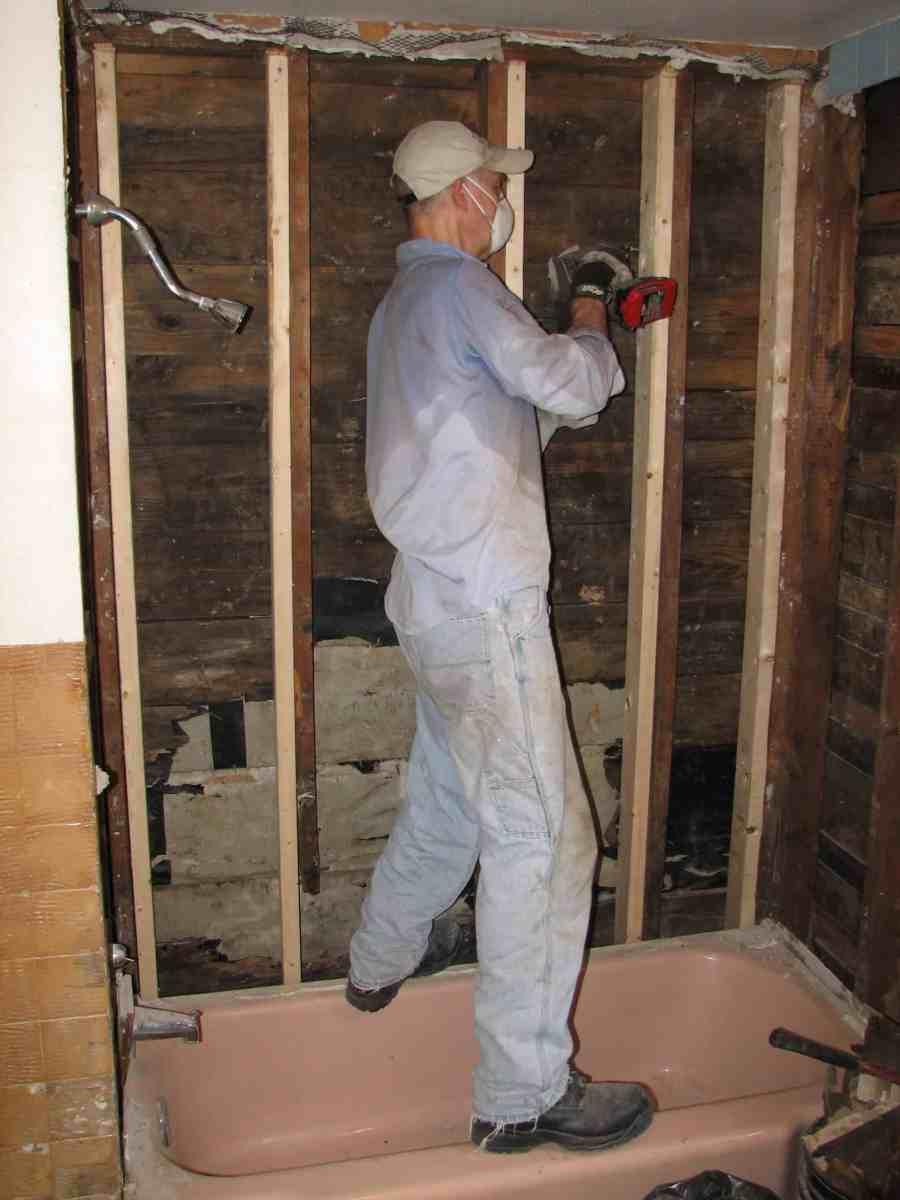 John repairing wall in an apartment bathroom as part of service with MCC SWAP in Elkhorn, WV.