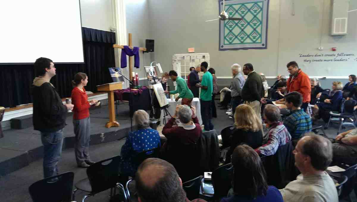 The Congregation adds finger prints to the heart that Luz has been painting during the worship service on Dec. 21, 2014 .