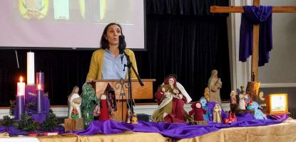 Melissa preaching Dec. 17, 2017 with many Marys on the table in front of her.