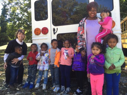 Growing Together Preschool class with their teachers by their school bus