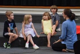 Melissa talking with children up front during RMC worship