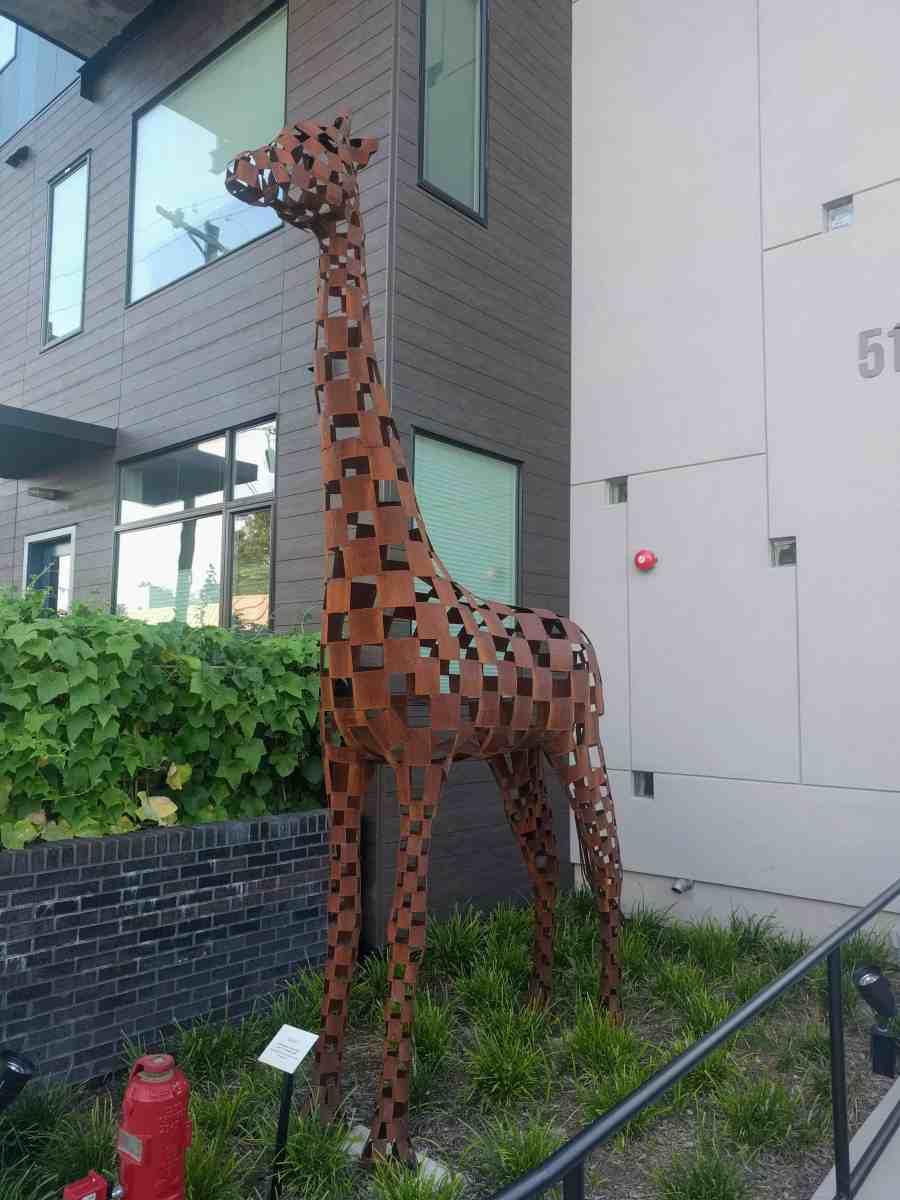 Metal statue of a giraffe in front of condominium.