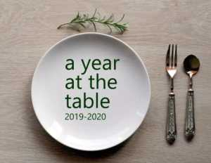 """A table place setting with """"A Year at the Table, 2019-2020"""" written on the place."""
