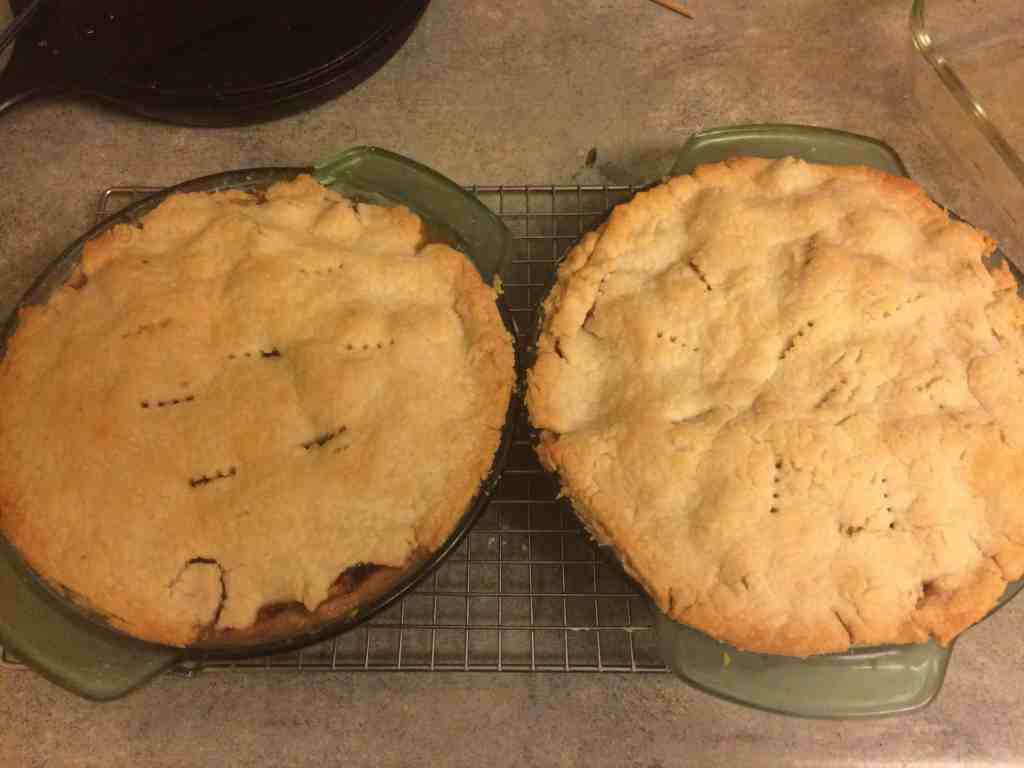 Two fresh apple pies on a baking rack.