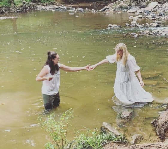 Elizabeth in white dress wades into the river, with Melissa standing in the river holding her outstretched hand.
