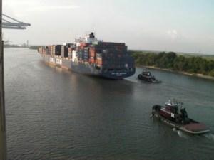 Tugs escort a freighter down the Savannah River.