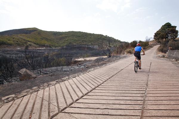 Un ciclista circula entre las zonas quemadas de Ruizgomez y Erjos