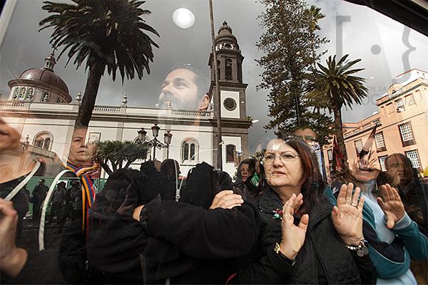 Algunas personas contemplan las manifestaciones desde la mampara de un establecimiento situado frente a La Catedral de La Laguna inaugurada hoy por el Ministro de Educación, Cultura y Deportes, José Ignacio Wert