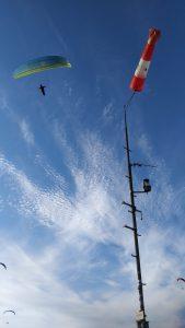 Vrcholový stožár a letící paraglidista