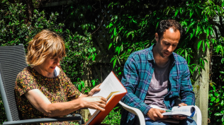 Anna Jackson and Luc Arnault reading in the sun