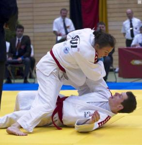 Image of a woman performing a jujitsu hold on her male opponent