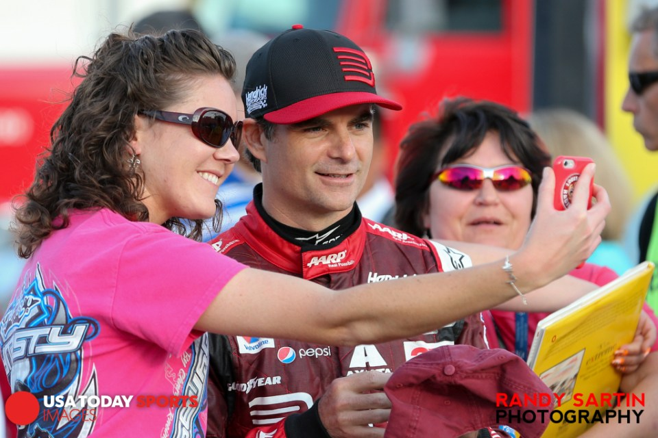 May 21, 2015; Concord, NC, USA; NASCAR Sprint Cup Series driver Jeff Gordon (24) has a selfie taken with fans before qualifying for the Coca-Cola 600 at Charlotte Motor Speedway. Mandatory Credit: Randy Sartin-USA TODAY Sports