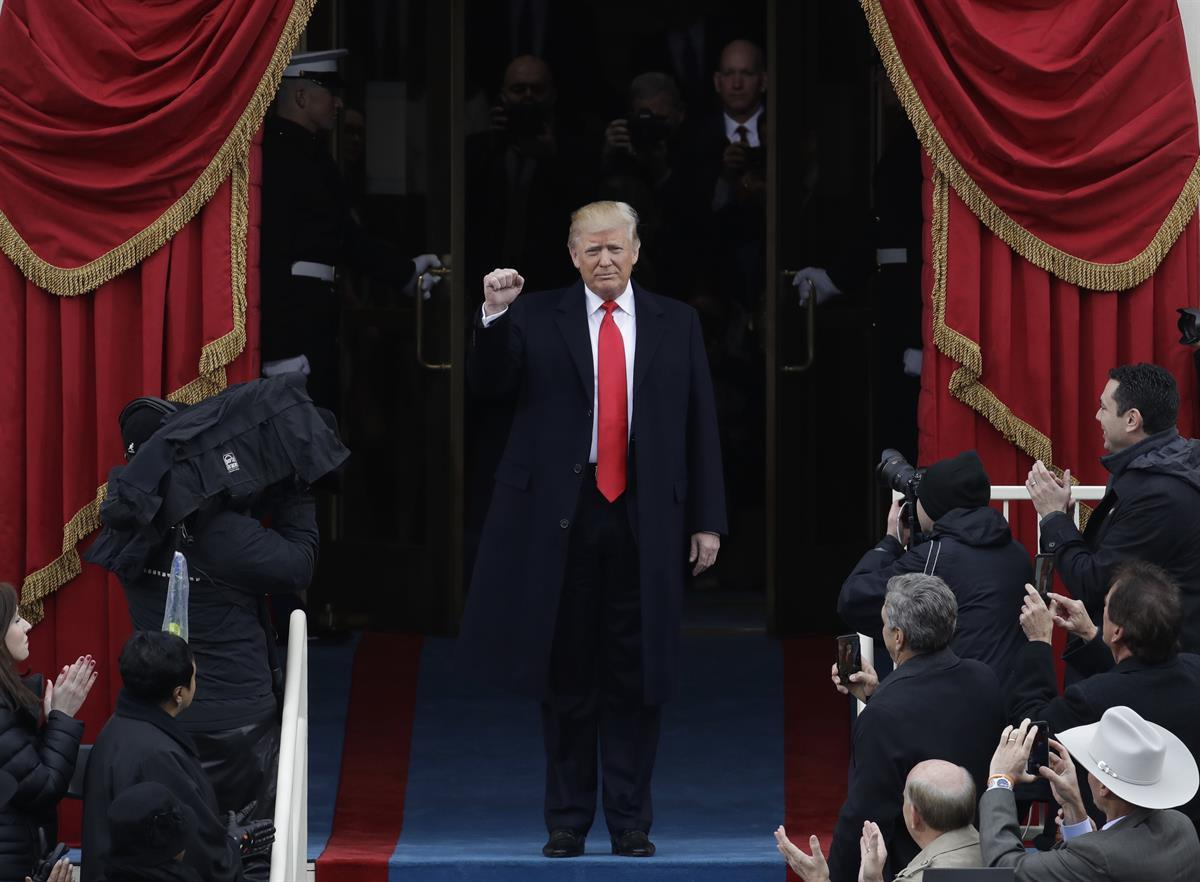President Donald Trump pumps his fist as he arrives for his Presidential Inauguration at the U.S. Capitol in Washington. Jan. 20, 2017. (AP Photo/Patrick Semansky)