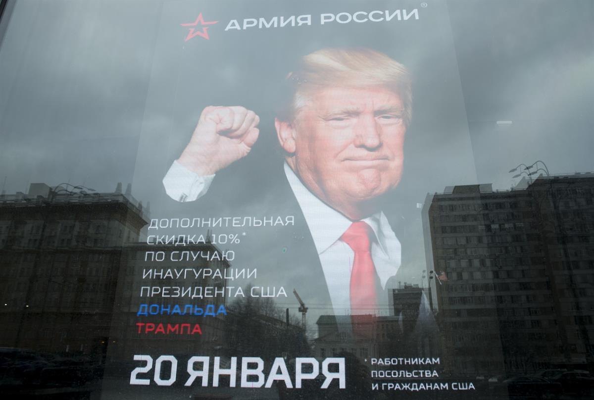 "The U.S. Embassy is reflected in a window of a shop in Moscow, Russia. Jan. 20, 2017. The poster reads: ""10 percent discount to the embassy employees and US citizens on the Inauguration Day"". (AP Photo/Pavel Golovkin)"