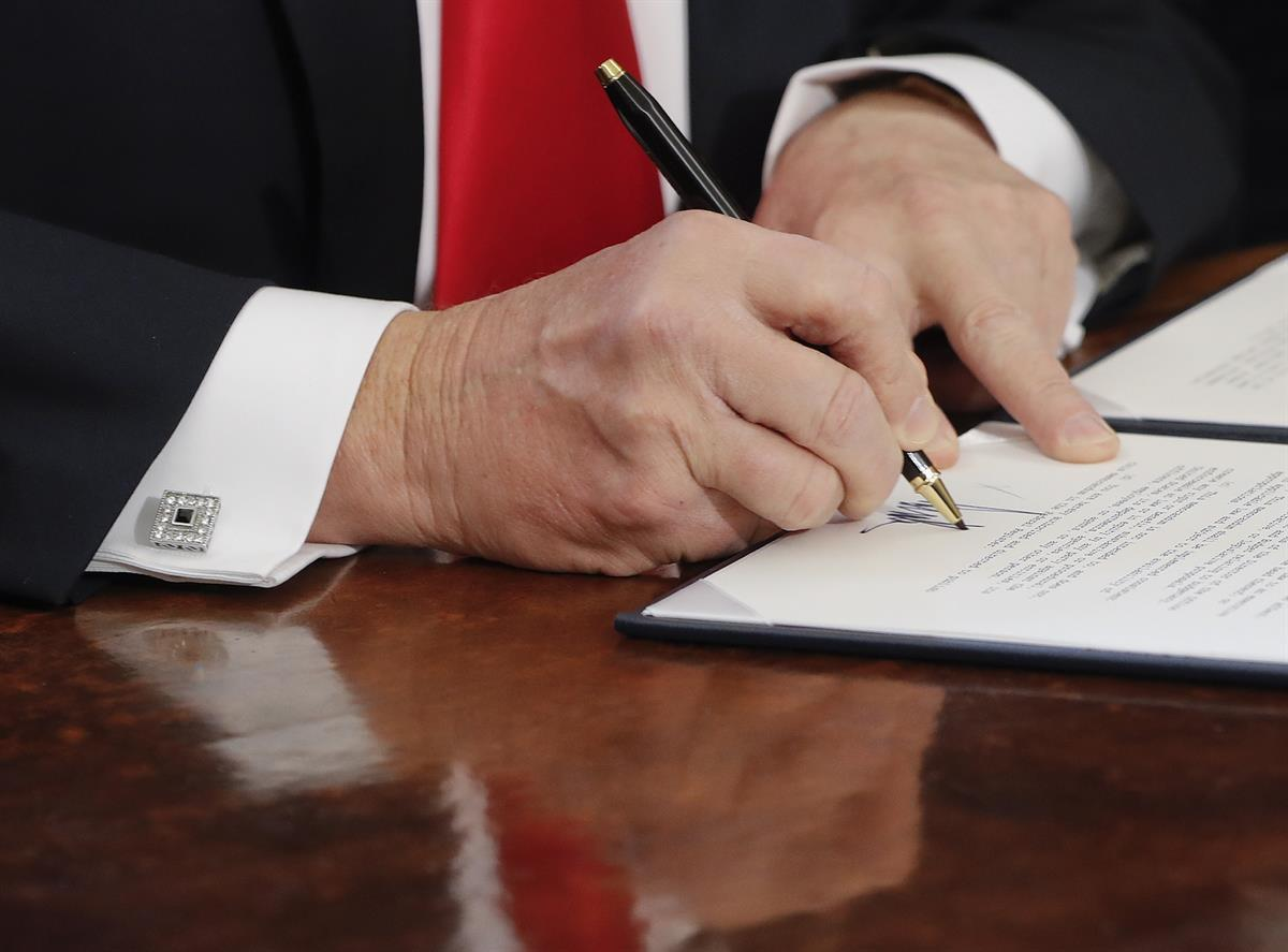 President Donald Trump signs an executive order in the Oval Office of the White House in Washington. Friday, Feb. 3, 2017. (AP Photo/Pablo Martinez Monsivais)