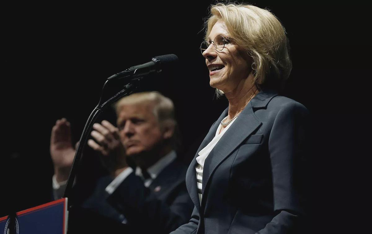 "Donald Trump applauds as Betsy DeVos speaks at Trump's ""Thank You USA"" rally in Grand Rapids, December 9, 2016. (Reuters/Mike Segar)"