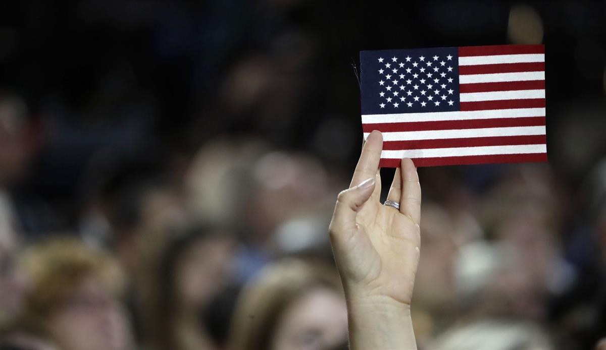 A small American flag is held aloft during Democratic presidential nominee Hillary Clinton's election night rally in the Jacob Javits Center glass enclosed lobby in New York, Tuesday, Nov. 8, 2016. (AP/Frank FranklinII)