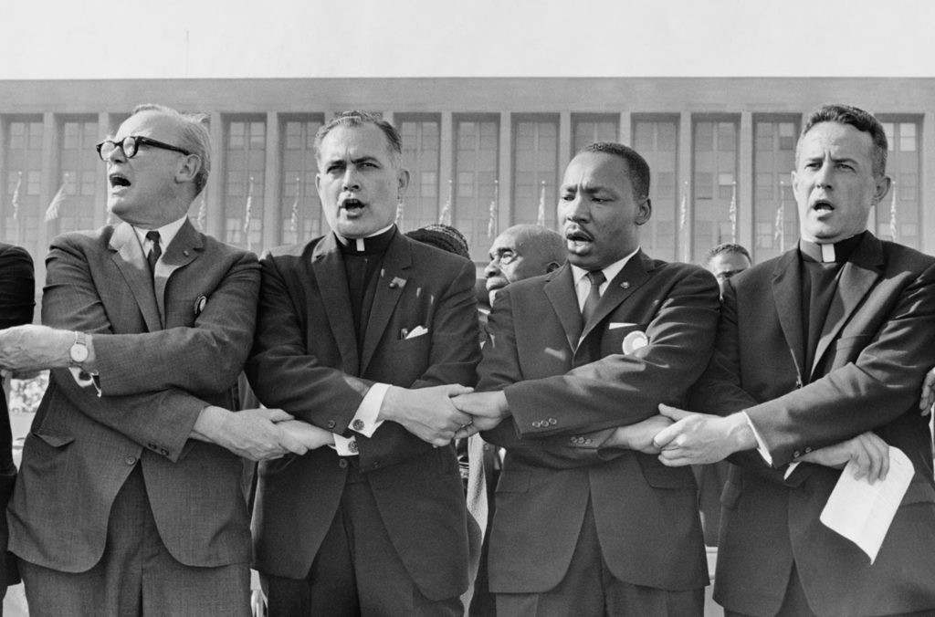 Rev. Theodore M. Hesburgh with Martin Luther King Jr., Rev. Edgar Chandler (far left), and Msgr. Robert J. Hagarty of Chicago (far right) at the Illinois Rally for Civil Rights in Chicago's Soldier Field, 1964